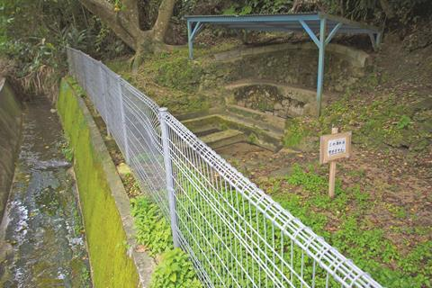 An image showing a sign posted by town officials to warn people not to drink nearby polluted spring water is pictured in Kadena, Okinawa, Friday, May 10, 2019