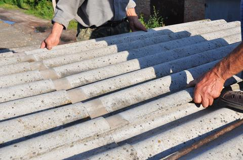 Roofers replace damaged asbestos tile