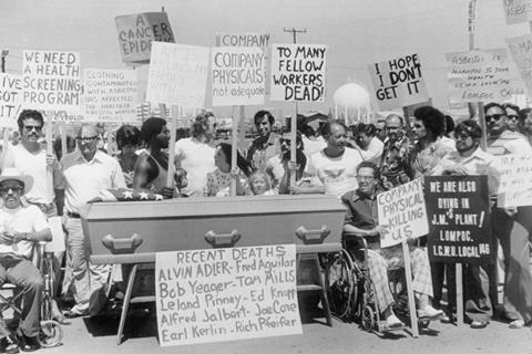 A group of asbestos workers line up by a coffin in protest