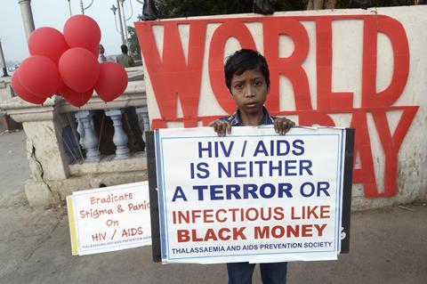 An Indian boy stands with a awareness placard during a HIV/ AIDs awareness program on the occasion of World AIDS Day on November 30, 2016 in Calcutta, India.