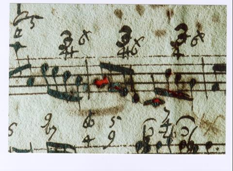 A musical score with holes from iron gall ink corrosion