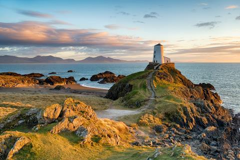 Sunset at Ynys Llanddwyn island on the coast of Anglesey in North Wales with the mountains of Snowdonia in the distance