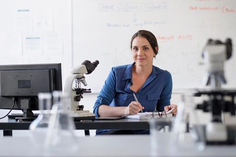 Woman sat in a lab writing on some paper