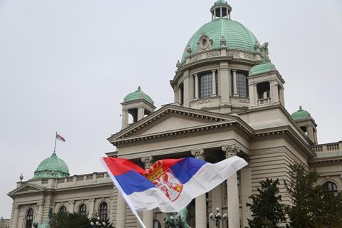An image showing a Serbian flag in front of the Serbian Parliament building