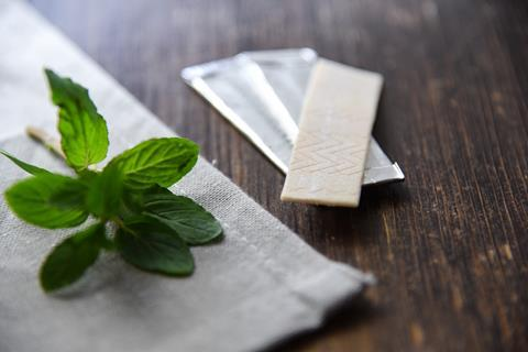 Chewing gum with a mint leaf on a wooden table