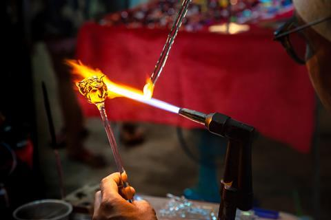 Glassblower made handicraft from melted glass roses shaped at the end of glassblowing pipe