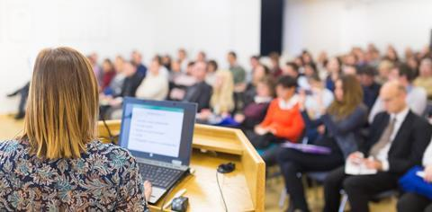 A speaker with a laptop presents to a conference audience