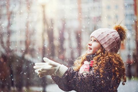 A young girl catching falling snow
