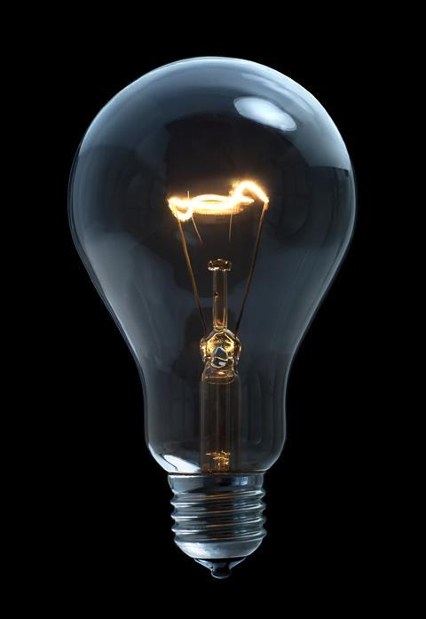 A incandescent light bulb on black background