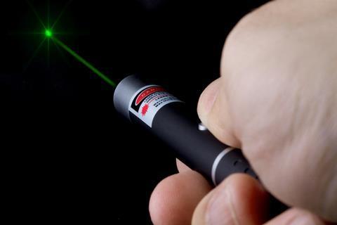 Hand holding a high power green laser pen