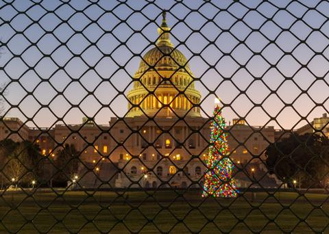 A picture taken during the sunrise over the United States Capitol Building and the Capitol Christmas Tree, now fenced off from the public during the government shutdown.