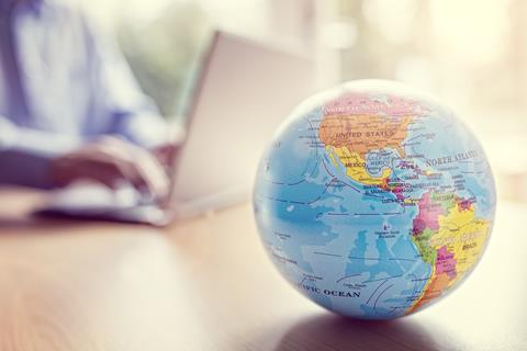 A globe map on a table in front of a man working on a laptop