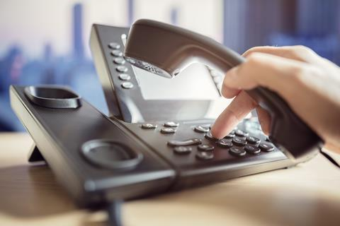 Person's hand dialling a telephone