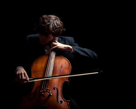 Man playing cello, dark background