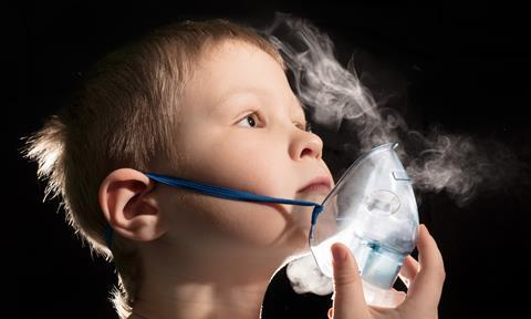 Child inhaling vapour through a nebuliser mask