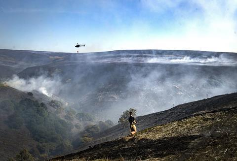An image showing a firefighter tackling the wildfire on Saddleworth Moor