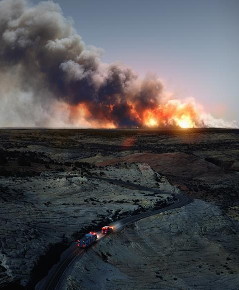 An image showing a landscape where a big wildfire can be seen on the horizon