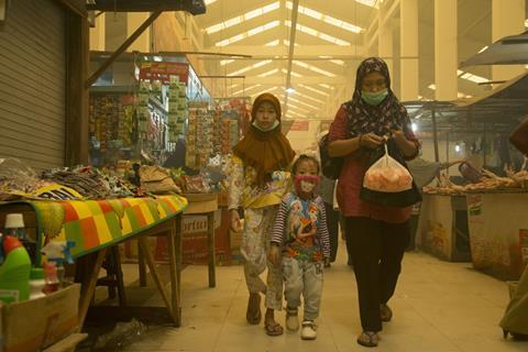 An image showing a mother with her two children walking through a market in Palangka Raya; they are wearing face masks as the space is filled with smoke produced by a wildfire, which also obstructs visibility