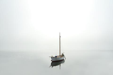 Sailboat in calm but foggy water