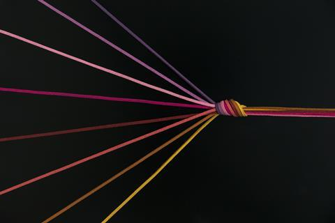An image showing colourful suede cords converging into a knot which them continues as a complex thread