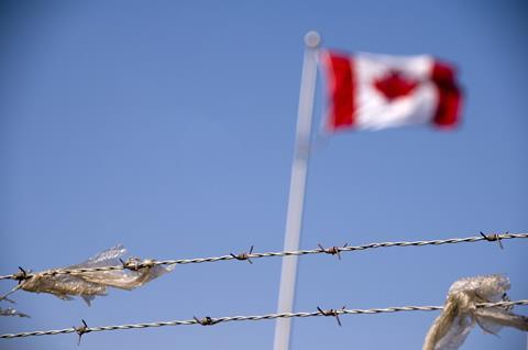 The Canadian flag behind barbed wire