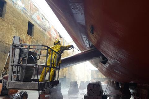 Worker washing ship hull at drydock
