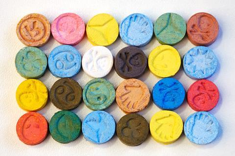 Several pills of MDMA (Extasy) on white table
