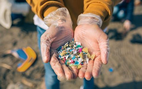 Someone holding small pieces of plastic on a beach