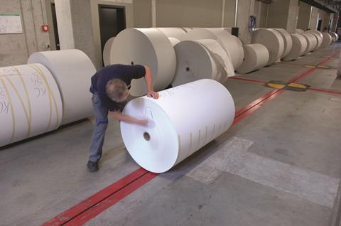 Man marking roll of printing paper