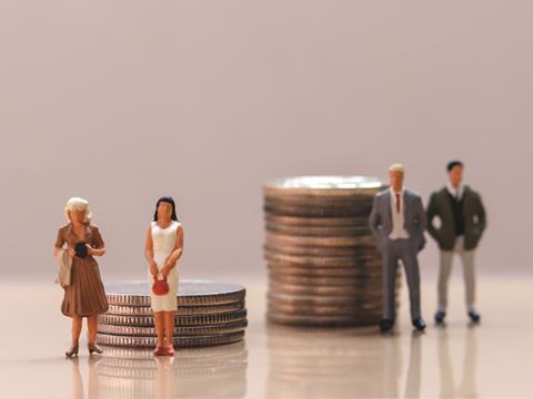 Mini male and female model figures stood near pile of coins