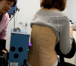 Woman having her back analysed by a machine