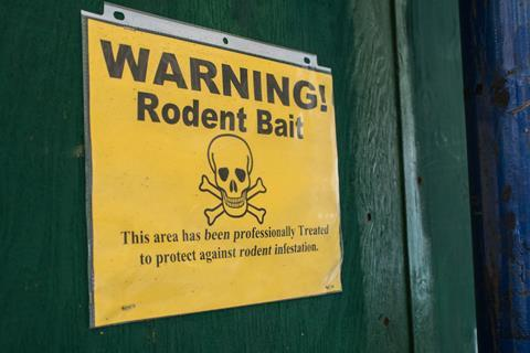 Rodent bait warning post on a building wall