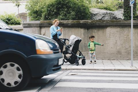 An image showing a woman and her child crossing a street on the zebra