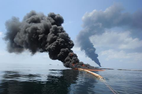An image showing dark clouds of smoke and fire emerging as oil burns during a controlled fire in the Gulf of Mexico