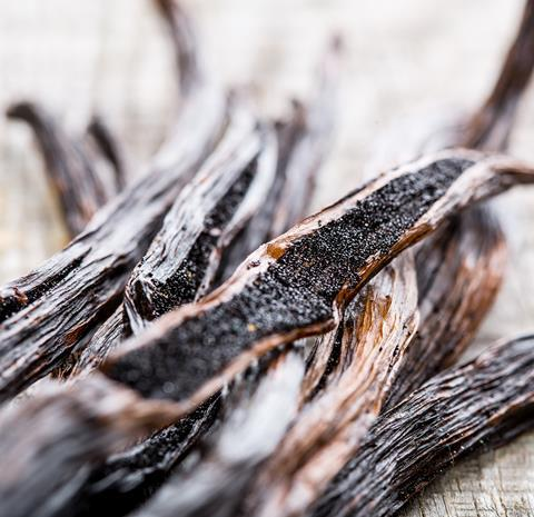 A close up of vanilla pods on a wooden table