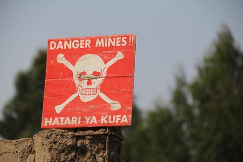 White skull-and-crossbones symbol on a red sign warning of the danger of landmines, Democratic Republic of Congo