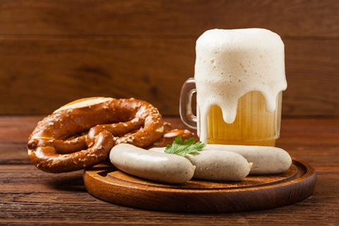 A photograph of beer, white sausages and pretzels