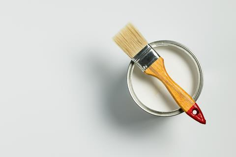 A can of white paint with a paintbrush