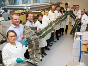 scientists holding long flexible solar cell