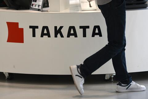 Visitor walking past Takata sign in vehicle showroom - original