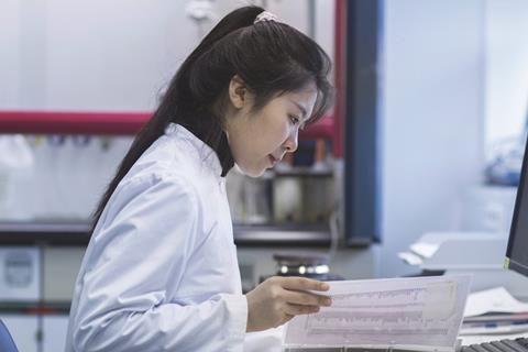 Female scientist reading documents in lab