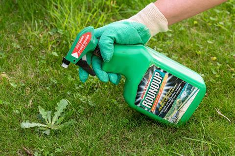 An image showing Roundup being sprayed on grass