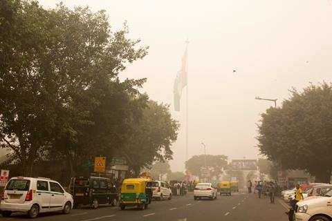 New Delhi, India, November 08, 2017: People driving on a fog coverd road in a busy afternoonn at central city area of New Delhi