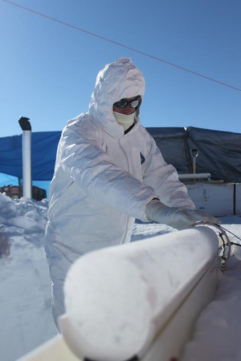 A photograph of a scientist working on an extracted ice core