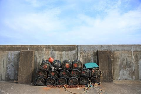 Stack of lobster pots against a sea wall