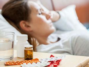 Person sleeping with pills beside them