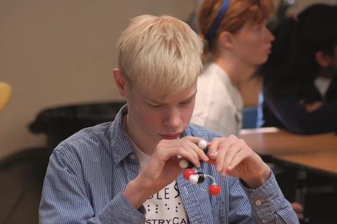 A visually impaired student holding a molecular model