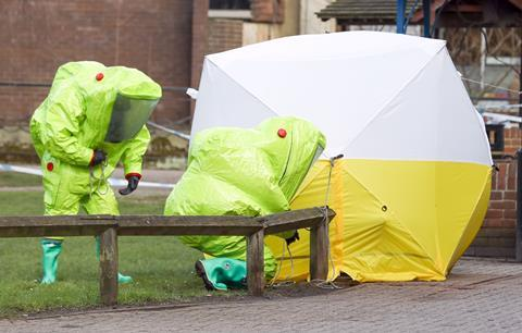 Investigators wearing hazmat suits whilst securing a tent for investigations into the Novichok poisonings