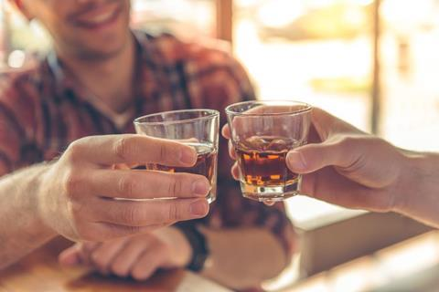 An image of people clinking whiskey glasses