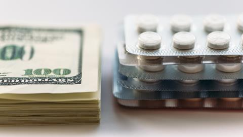 100 dollar bills stacked up on the left and on the right packets of medication
